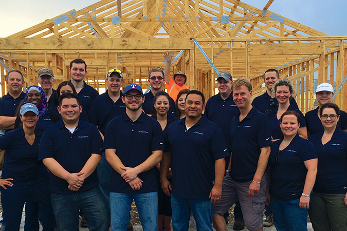 Team of Argo employees standing in front of a framework for a new house.